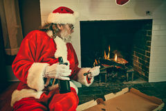 Bad Santa Reheating Pizza In The Fireplace. Bad Santa getting drunk and Reheating Pizza In The Fireplace Royalty Free Stock Photos
