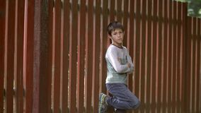 Bad serious boy stands near a wooden fence and looks into the camera. Have fun royalty free stock photos