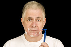 Bad Shave Second Revision. A man looks unhappy after having to shave his beard.  Tissue paper sticks to the rough spots Royalty Free Stock Photo