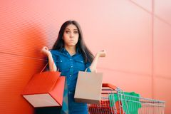 Unhappy Shopper Woman with Shopping Cart in front of Store. Bad shopping experience no client satisfaction concept image Royalty Free Stock Images