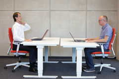 Bad sitting position at workstation correction. Man working in correct sitting posture in office watching his colleague sitting in bad position at workstation Royalty Free Stock Photos
