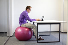 Bad sitting posture at tablet. Business man on stability ball in his office royalty free stock images