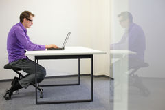 Bad sitting posture at workstation. man on kneelin Stock Image