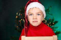 Bad small boy in santa hat Royalty Free Stock Photo