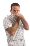 Bad Smell. A young man holding his nose because of a bad smell, isolated against a white background Stock Image