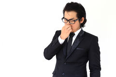 Bad Smell. The Asian businessman holding his nose with his hand stock photo