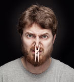 Bad smell concept - peg on male nose. Bad smell concept - peg on male nostrils over black Stock Photography