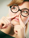 Girl pinches her nose because of stench stink. Bad smell concept. Young woman feels disgust pinches her nose with fingers because of odor stench unpleasant royalty free stock photo