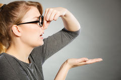 Girl pinches her nose because of stench stink. Bad smell concept. Young woman feels disgust pinches her nose with fingers because of odor stench unpleasant royalty free stock photos