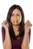 Bad smell. Disgusted young woman pinching her nose with a clothespin royalty free stock image