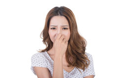 Bad smell face. Portrait of a young woman holding her nose because of a bad smell royalty free stock images