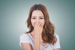 Bad smell face. Portrait of a young woman holding her nose because of a bad smell royalty free stock photo
