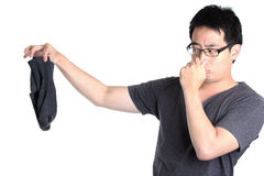 Bad smell. Man keep socks with bad smell and hand plug nose, isolated white royalty free stock photography