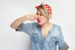 Bad smell. Portrait of dissatisfied beautiful young woman in casual blue denim shirt with makeup and red headband standing. Pinching her nose. indoor studio royalty free stock photography