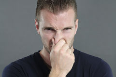 Bad smell. Portrait of a man pinching his nose on a gray background stock photo