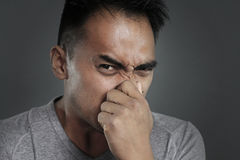 Bad smell. Portrait of a man pinching his nose on a gray background stock photography