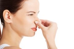 Bad smell. Portrait of a young woman holding her nose because of a bad smell stock images