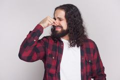 Bad smell. Squeamish man with beard and black long curly hair in. Casual style, checkered red shirt standing blocking his nose because bad smell. indoor studio stock photos