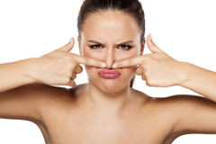 Bad smell. Young woman closes her nose because of the smell royalty free stock image