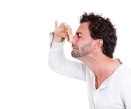 Bad smells. Closeup side view portrait of young man, disgust on his face, pinching nose, something stinks, very bad smell, odor, situation, isolated on white royalty free stock photography