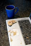 Bad Start. What a horrible way to start the day. Spilled my coffee all over my laptop. As I went to grab the cup, my cookie crumbled royalty free stock image