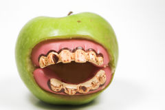 Bad teeth. A granny smith apple with a set of false teeth Stock Photo