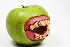 Bad teeth. A granny smith apple with a set of false teeth Royalty Free Stock Photography