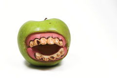 Bad teeth. A granny smith apple with a set of false teeth Royalty Free Stock Photos
