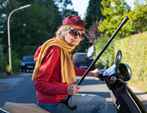 Bad tempered old woman with a walking stick. Shaking it in the air as she rides along on her scooter dressed in a trendy cap and scarf Royalty Free Stock Photography