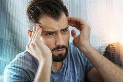 Deep serious man looking aside and touching to his head. Bad thoughts. Deep serious unshaken man looking aside feeling bad himself and touching to his head Stock Photos