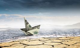 Bad times in business . Mixed media. Dollar banknote ship in desert as symbol for financial crisis . Mixed media Stock Photography