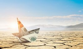 Bad times in business . Mixed media. Dollar banknote ship in desert as symbol for financial crisis . Mixed media Royalty Free Stock Photos