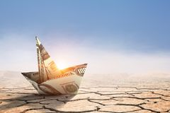 Bad times in business . Mixed media. Dollar banknote ship in desert as symbol for financial crisis . Mixed media Royalty Free Stock Photography