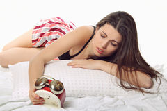 Bad wake up. Girl looks worried by unpleasant the alarm clock . Bad wake up concept Stock Photos