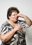 Bad water. An older hispanic woman pinches her nose after smelling her water bottle Royalty Free Stock Photography