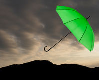 Bad weather background. Green umbrella over stormy sky. Royalty Free Stock Photo