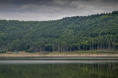 Bad weather. Sad rain clouds landscape water ake lake green tree treen woods forest reflection stock image