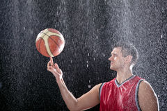 Basketball player spinning ball on a big rain. During bad weather, basketball player is practicing, preparing himself for a big match, while big rain is falling Stock Image