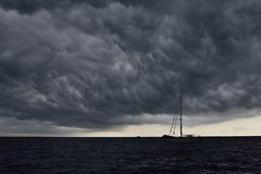 Bad weather is coming. Sailing boat at anchor off mthe coast of Corsica. The black clouds of the atmospheric front covers the sky. Bad weather and strong wind stock image