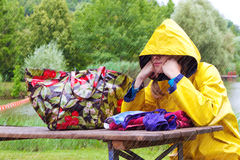 Bad weather day. Young woman in a yellow raincoat sitting frustrated on a lake Stock Images
