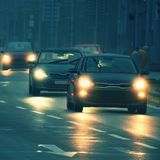 Cars in the fog. Bad winter weather and dangerous automobile traffic on the road. Light vehicles in foggy day royalty free stock photo