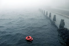 Bad weather on the embankment. Bad weather with mist on the embankment with redlife-buoy on the water Royalty Free Stock Images