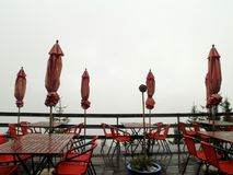 Bad Weather. Empty tables and chairs on a rainy top deck royalty free stock image
