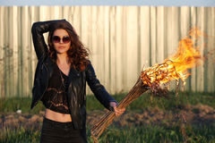 The bad woman in sunglasses and a black jacket holding a torch Outdoors Royalty Free Stock Images