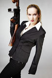 Bad woman with tommy gun. Mafia style fashion studio portrait - nice young woman posing with Tommy gun for figure and portrait photos in retro criminal style stock image