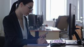 Bad work, businesswoman wearing glasses while using computer and mobile phone in office. Bad work, businesswoman wearing eyeglasses while using computer and stock footage