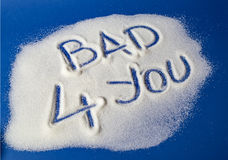 BAD FOR YOU written with  sugar. Sugar on a blue background with warning message BAD 4 YOU written on it. Health concept. Diabetes hazard Stock Photo