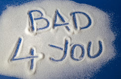 BAD FOR YOU written with  sugar. Sugar on a blue background with warning message BAD 4 YOU written on it. Health concept. Diabetes hazard Stock Images
