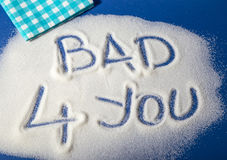 BAD FOR YOU written with  sugar. Sugar on a blue background with warning message BAD 4 YOU written on it. Health concept. Diabetes hazard Royalty Free Stock Photography