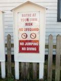 Bada på egen risk ingen livräddare ingen banhoppning ingen dykningvarning Arkivfoton